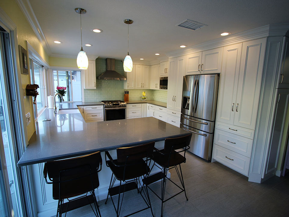 Transitional white kitchen remodel with custom cabinets in for G shape kitchen