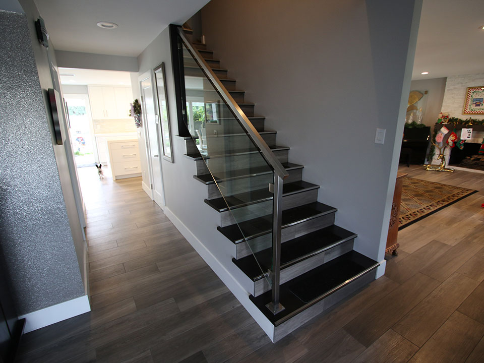 In Place Of Heavy, Dark Wood Steps There Are Now Black Stairs With Tile  Risers And A Glass And Steel Railing Floats Alongside The Stairs, Which  Makes Them ...